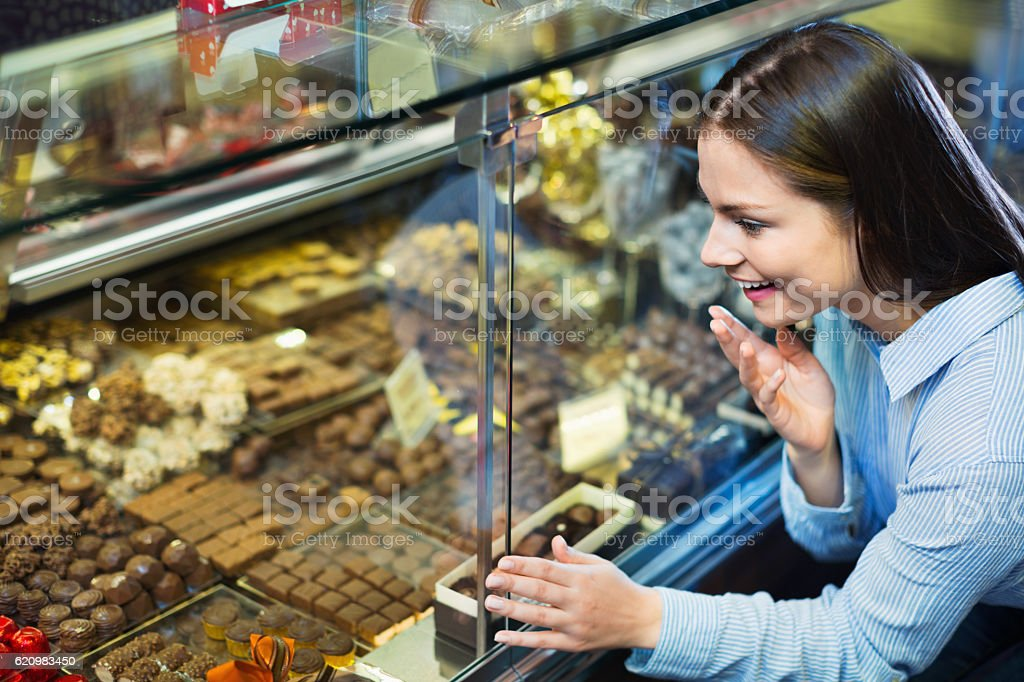 Smiling cheerful girl choosing delicious ganaches and chocolates foto royalty-free
