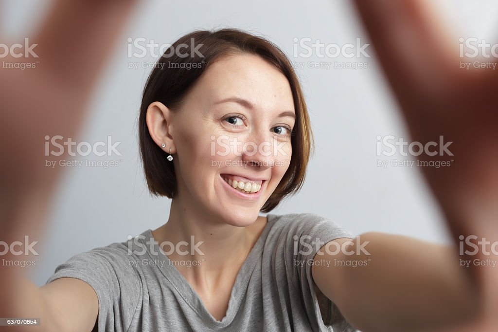 Smiling cheerful girl with freckles doing selfie. stock photo