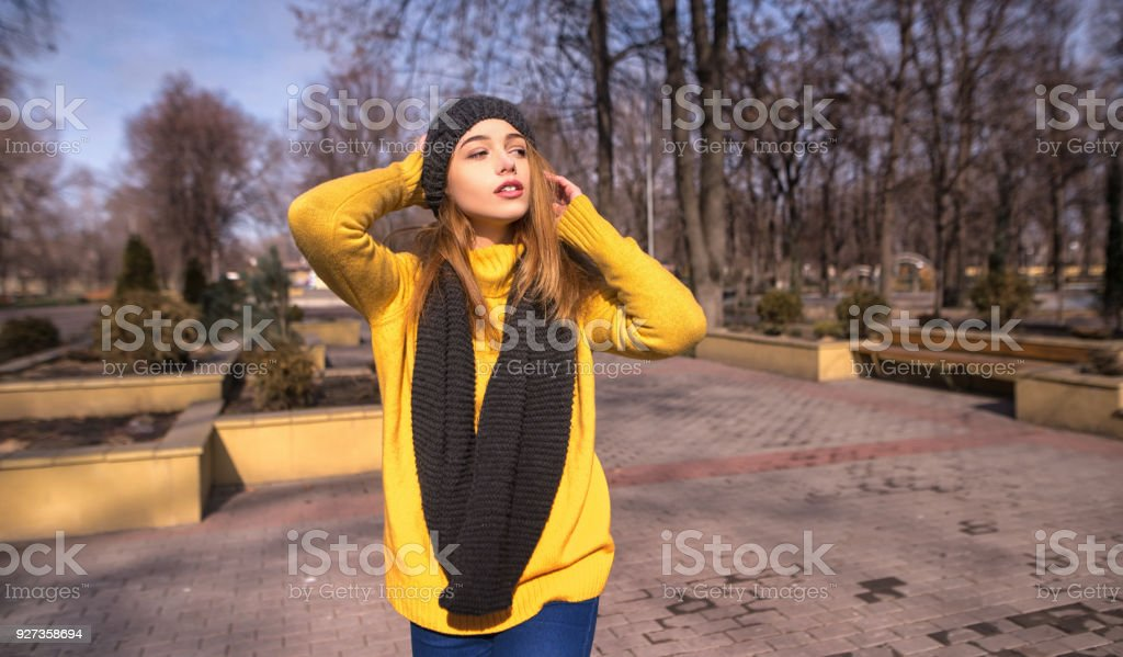 Smiling cheerful girl with long hair, wearing in black hat and yellow sweater, and enjoys freedom, standing next to road. Portrait of adorable young woman outside - Royalty-free Adult Stock Photo
