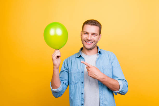 lächelnde fröhlichen kerl zeigt mit dem zeigefinger auf grüner ballon stehen auf gelbem hintergrund - ballonhose stock-fotos und bilder