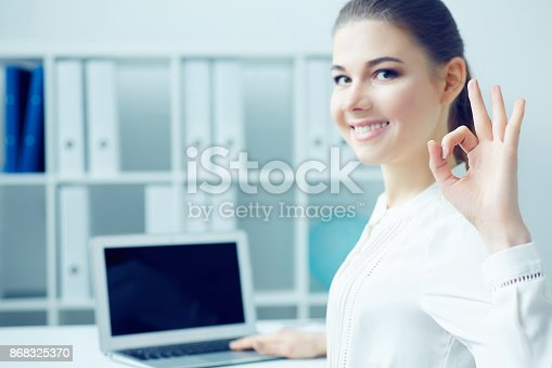 istock Smiling  cheerful student girl happy with completed work showing OK gesture, sitting half turn looking in camera while working on laptop.  Photo with depth of field. 868325370