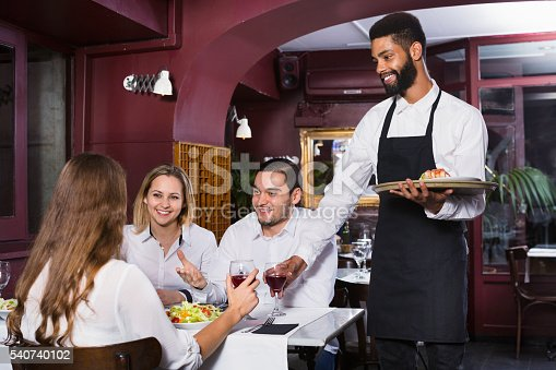 istock Smiling cheerful waiter taking care of adults 540740102