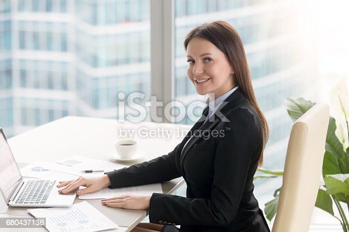 istock Smiling cheerful young businesswoman working at office desk with laptop 680437136