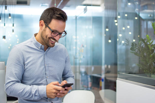 Smiling cheerful young man in smart casual wear holding smart phone and looking at it while standing in modern office. stock photo