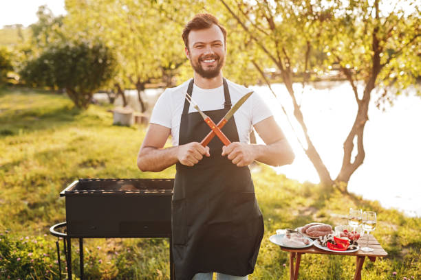 Smiling chef crossing utensils during picnic stock photo