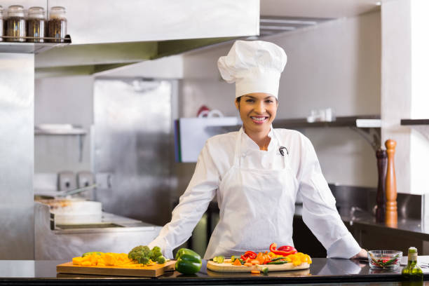 Smiling chef with cut vegetables in kitchen stock photo