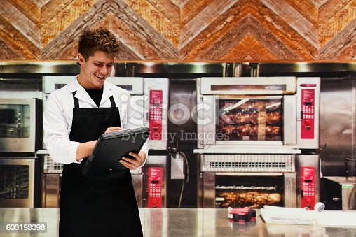 Smiling chef working with clipboard in kitchenhttp://www.twodozendesign.info/i/1.png