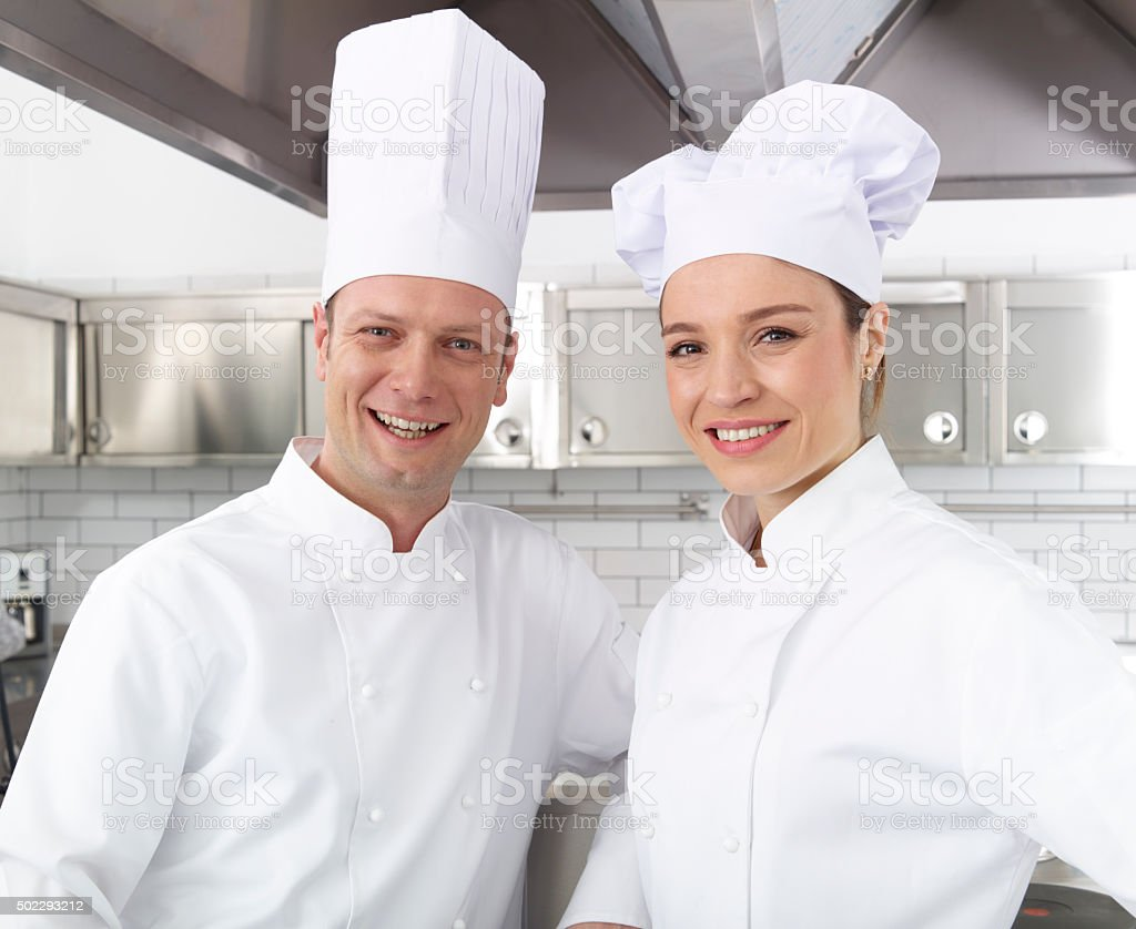 Smiling chefs looking at camera stock photo
