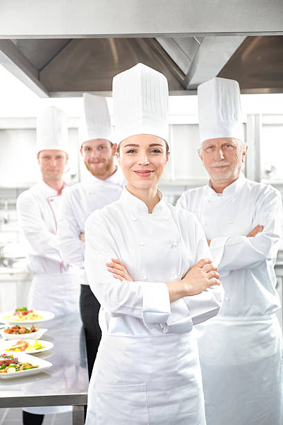 Smiling chefs looking at camera Chef's looking at camera in commercial kitchen chef's whites stock pictures, royalty-free photos & images