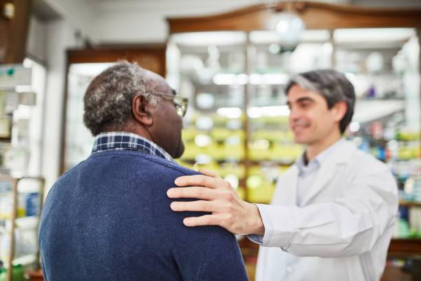 químico de sorriso que consolam o cliente sênior na farmácia - costumer - fotografias e filmes do acervo