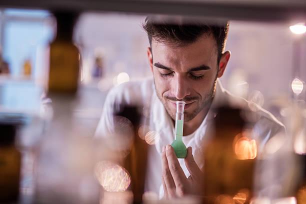 Lächelnd Chemiker riechen Stoffe in ein Becherglas in einem Labor. – Foto