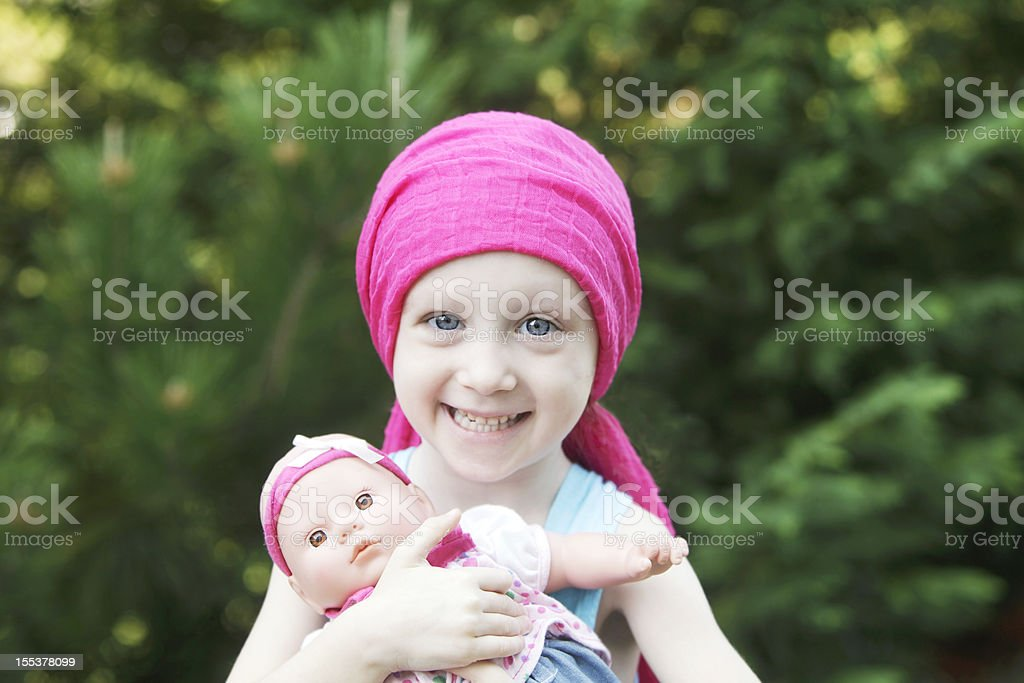 Smiling Chemo Child with Doll stock photo