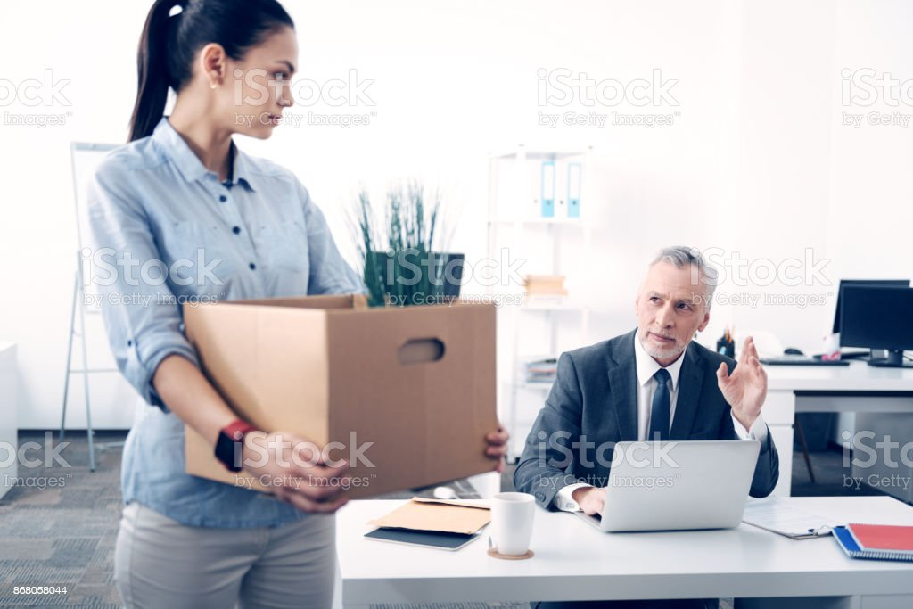 Smiling chief waving goodbye to former office worker stock photo