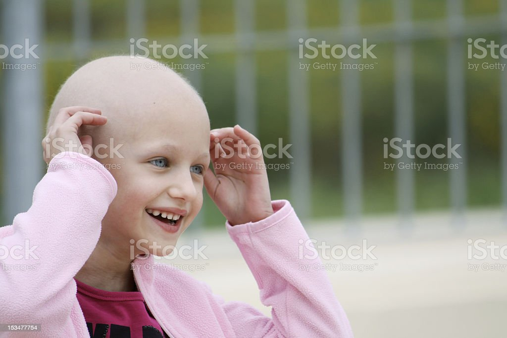 Smiling child cancer patient in pink stock photo