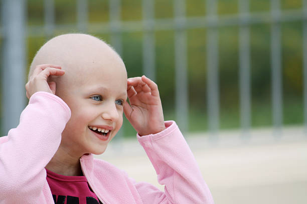 Smiling child cancer patient in pink beautiful caucasian girl undergoing chemotherapy treatment for cancer in her kidney chemotherapy cancer stock pictures, royalty-free photos & images