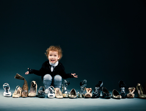 Smiling child choosing from a row of adult shoes stock photo
