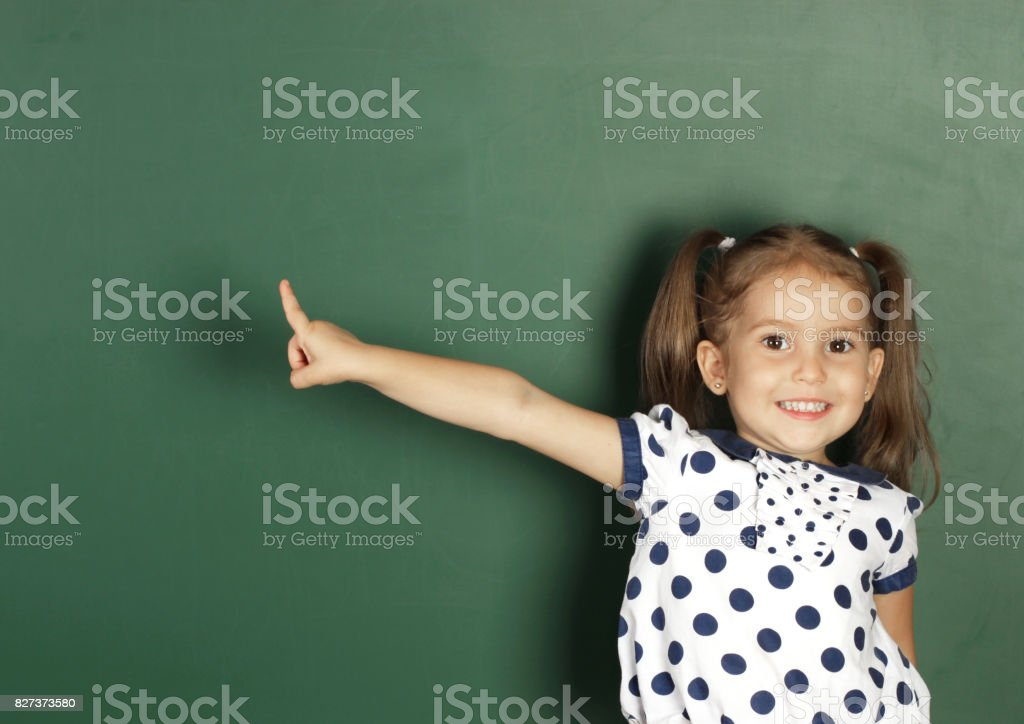 Smiling child girl show with a finger blank school blackboard stock photo