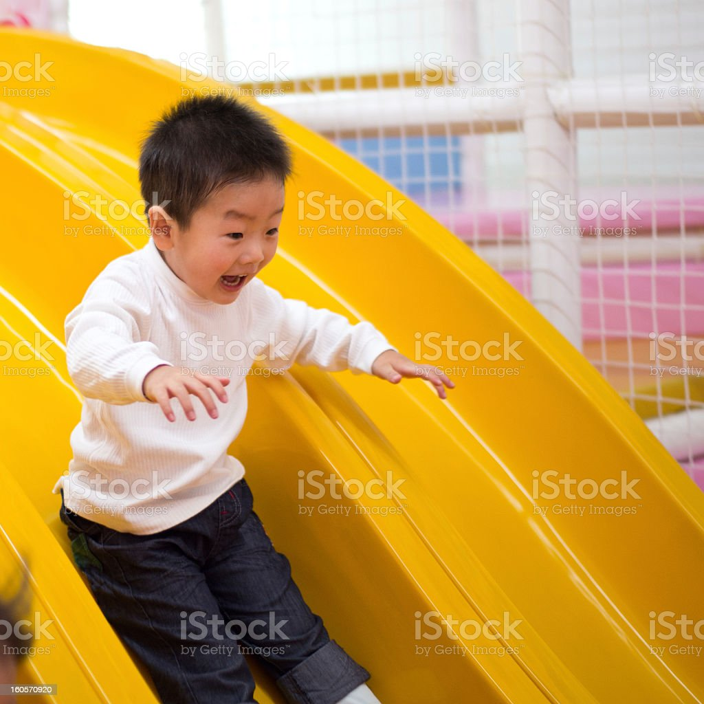 Smiling child going down a yellow slide stock photo