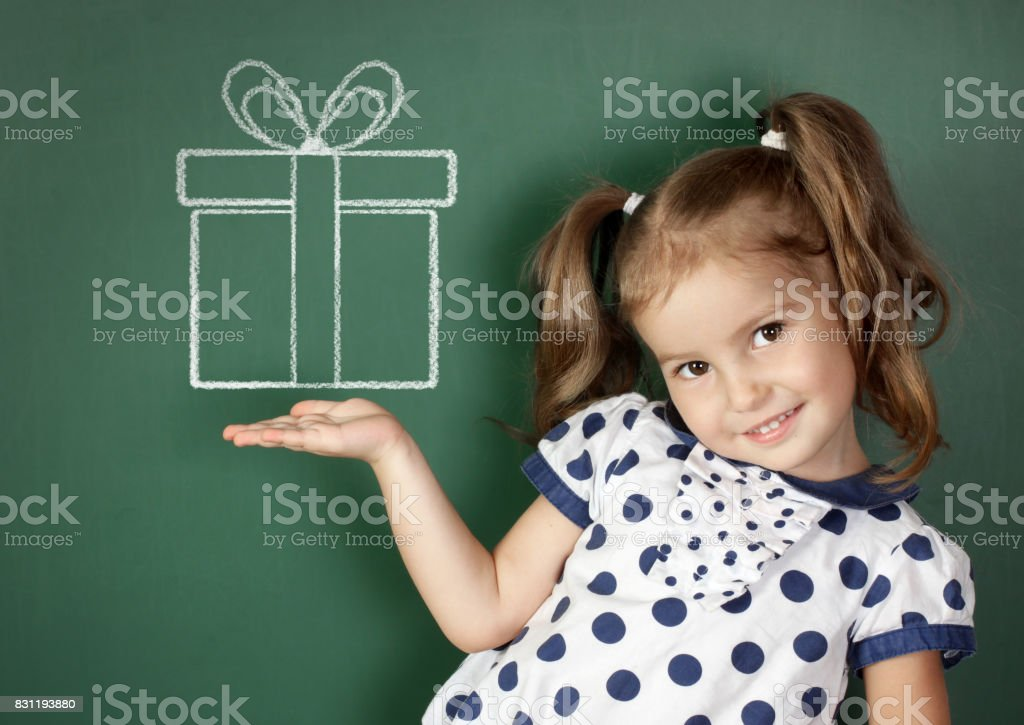 Smiling child hold drawn gift box near school blackboard stock photo