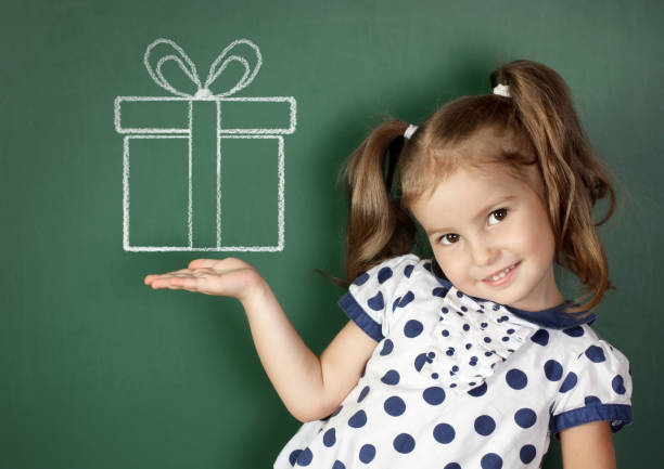 Smiling child hold drawn gift box near school blackboard stock photo