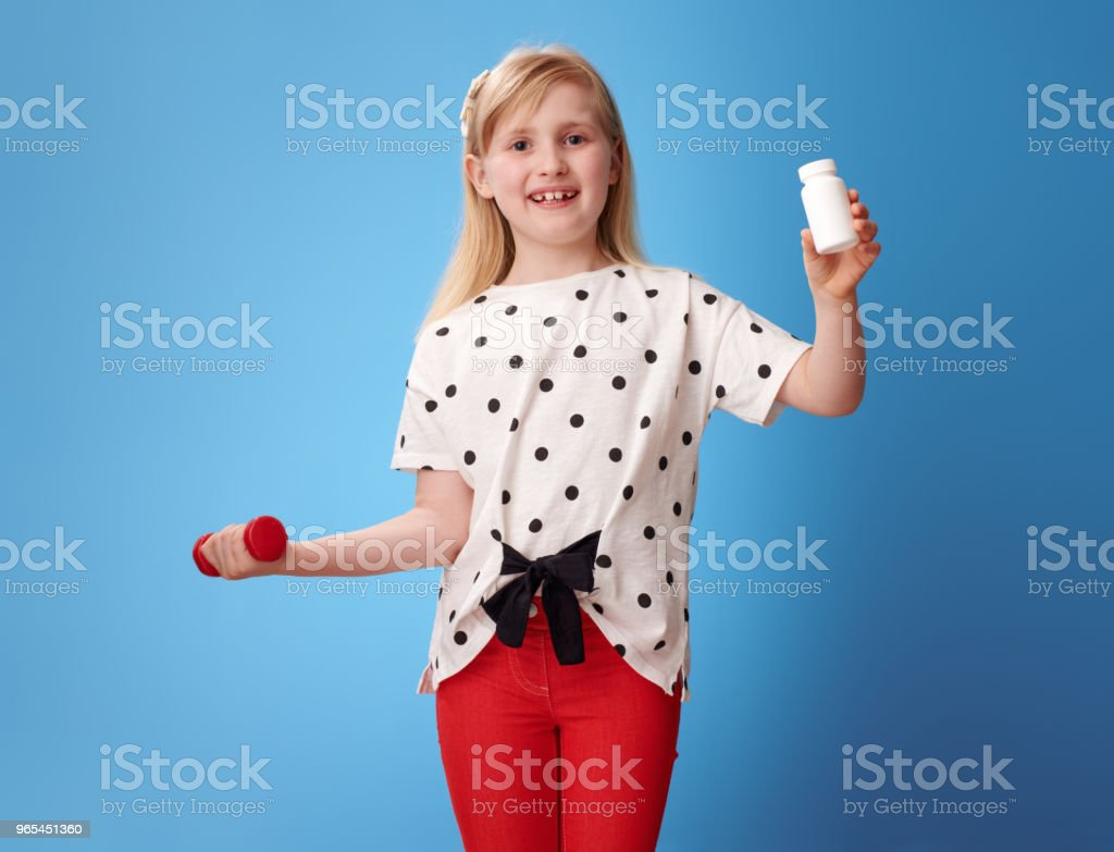 smiling child holding dumbbell and showing pills bottle on blue royalty-free stock photo