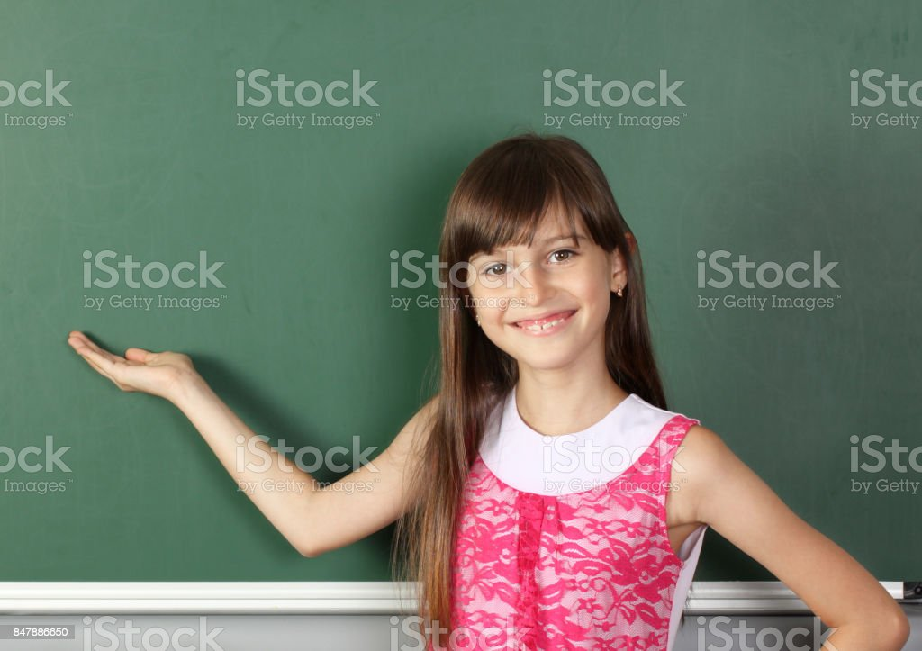 Smiling child holds his hand near empty school blackboard, copy space stock photo