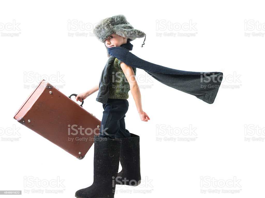 Smiling child in a fur hat and felt boots stock photo