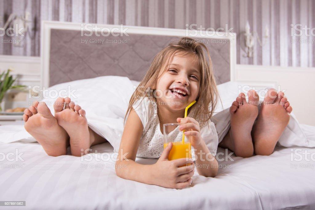 glimlachend kind in huis slaapkamer met ouders voeten op achtergrond royalty free stockfoto