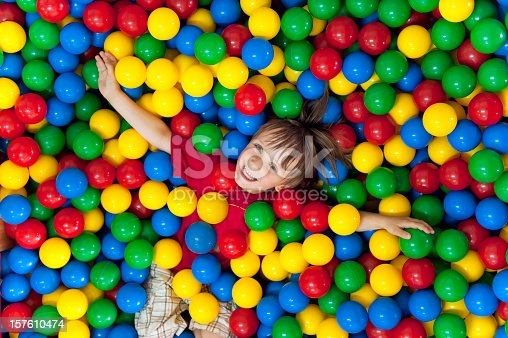 istock Smiling child playing in a colorful ball pit 157610474