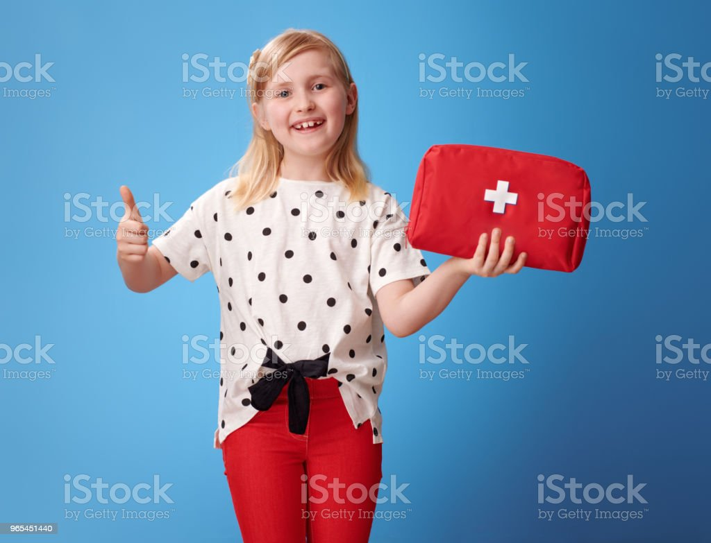 smiling child showing first-aid kit and thumbs up on blue zbiór zdjęć royalty-free