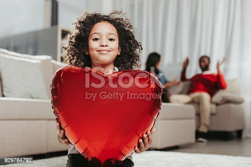 Happy childhood. Portrait of glad daughter holding air balloon in front of chest. Parents on background. Focus on girl