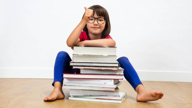 smiling child sitting behind many books with a thumbs up stock photo