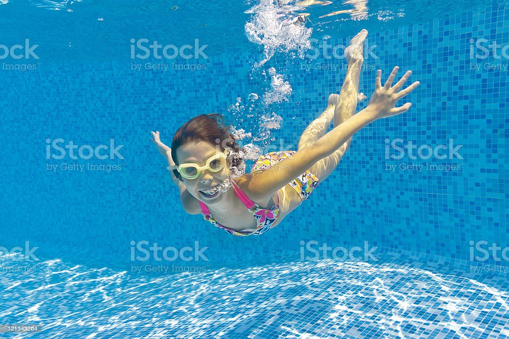 A smiling child swimming underwater in a pool in goggles stock photo