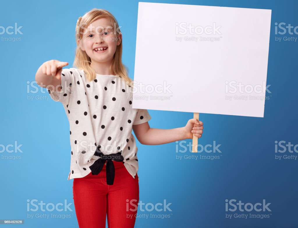 smiling child with blank poster pointing in camera on blue royalty-free stock photo