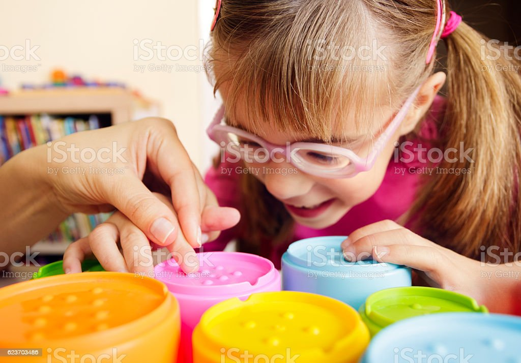 Smiling child with disability touching textured cups with her teacher stock photo
