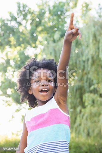 Smiling child with hand up in the park