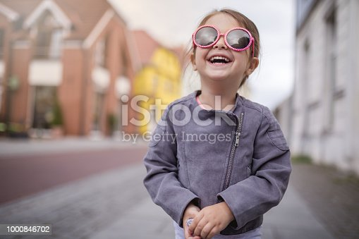 Lovely and beautiful child standing on a street in fashionable jacket.