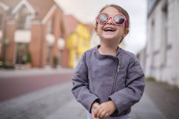 lächelndes kind mit sonnenbrille auf einer straße - sonnenbrille kleinkind stock-fotos und bilder