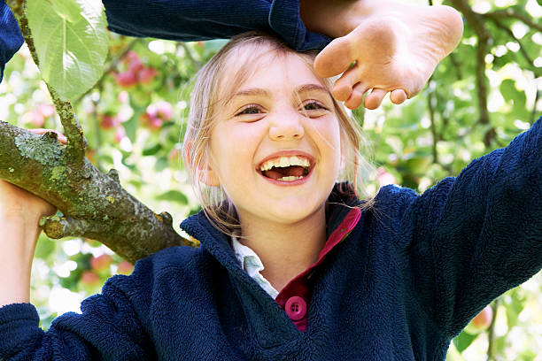 Smiling children climbing tree together stock photo