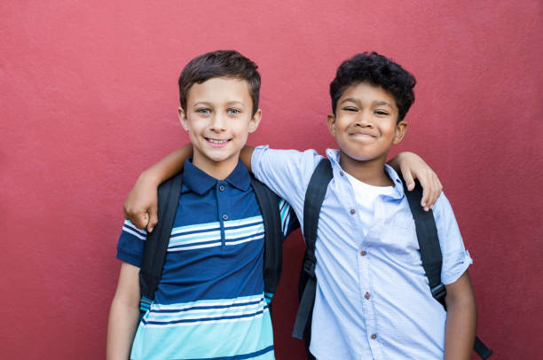 Smiling children friends embracing Best children friends standing with hand on shoulder against red background. Happy smiling classmates standing together on red wall after school. Portrait of multiethnic schoolboys enjoying friendship. 8 9 years stock pictures, royalty-free photos & images