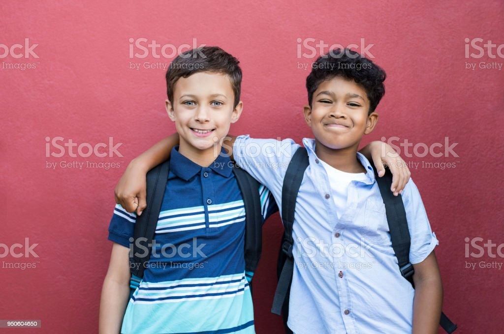 Amis de l'enfance souriant embrassant - Photo