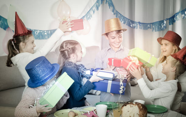 Smiling children handing gifts to birthday boy Smiling children handing gifts to birthday boy during dinner group of friends giving gifts to the birthday girl stock pictures, royalty-free photos & images