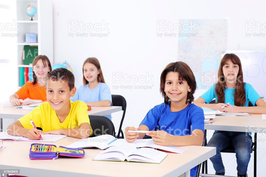 Smiling children sitting on a lesson. royalty free stockfoto