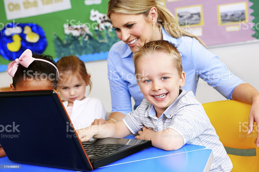 Smiling children using laptop computer with teacher royalty-free stock photo