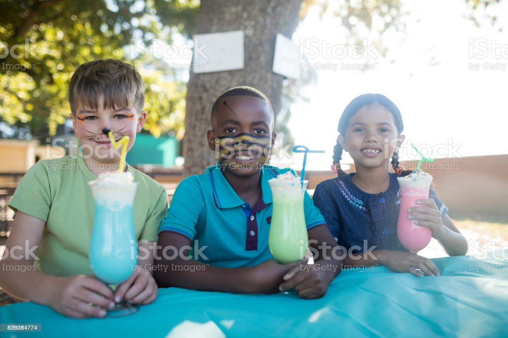 Smiling children with face paint having drinks at park stock photo