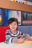 Smiling Chinese boy drawing