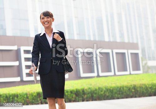 465474428istockphoto Smiling Chinese businesswoman walking 1083094002