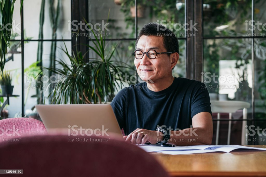 Smiling Chinese man working on laptop at home Mature man in glasses at home, typing on computer, contented, small business owner 50-59 Years Stock Photo