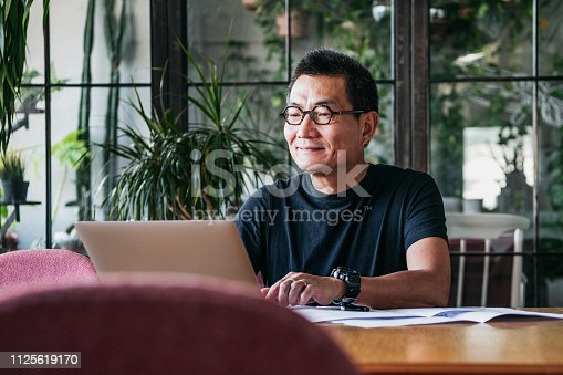 Mature man in glasses at home, typing on computer, contented, small business owner