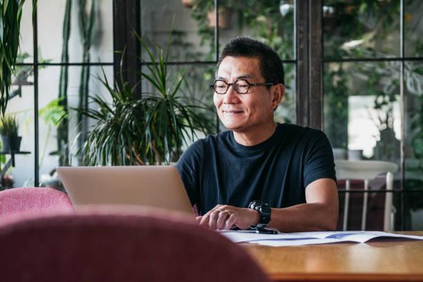 微笑的中國人在家裡做筆記本電腦 - 亞洲 個照片及圖片檔